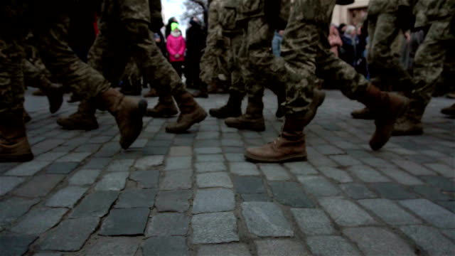 background with formation of soldiers in uniform marching on the pavement on the street video