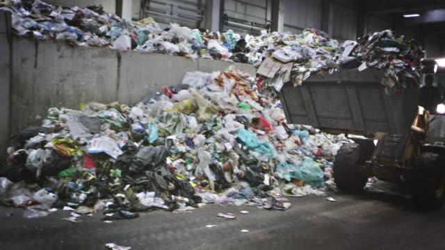 CS Backhoe loader loading the garbage onto a conveyor belt video