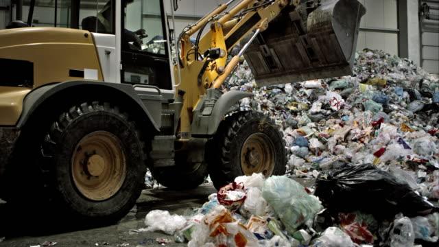 stockvideo's en b-roll-footage met backhoe loader stapelen zich op het afval in de faciliteit recycling - shovel