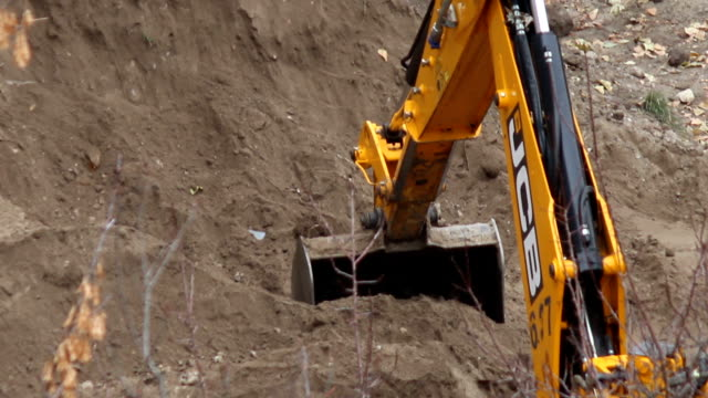 Backhoe tractor works on a construction site. video