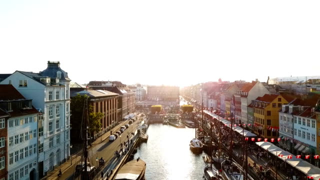 backlight sunset footage from copenhagen, denmark. bridge in nyhavn new harbour canal and entertainment district. aerial video footage view from the top. forward movement. sunset golden time light - копенгаген стоковые видео и кадры b-roll