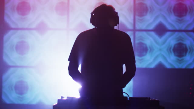 vídeos de stock e filmes b-roll de backlit dj playing music in nightclub. silhouette of a dj - retroiluminado