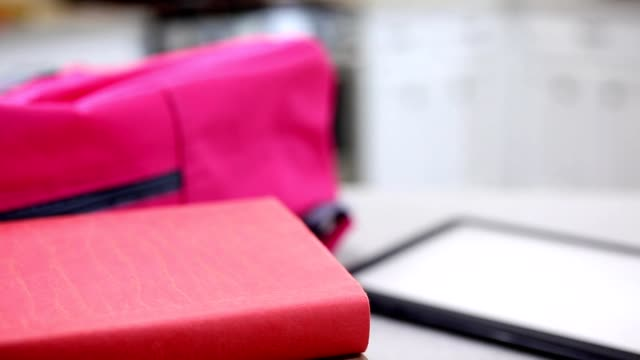 Backpack books and digital tablet on kitchen bar video