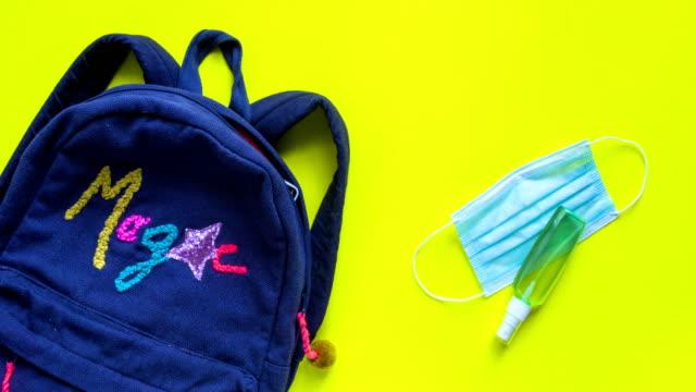 plecak z przyborami szkolnymi i środkiem odkażającej i medyczną maską ochronną zatrzymać animację ruchu. powrót do szkoły po kwarantannie koncepcji. - przybory szkolne filmów i materiałów b-roll