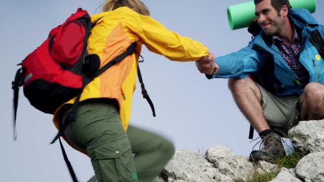 vídeos y material grabado en eventos de stock de mochilero subir a la montaña - escalada en rocas