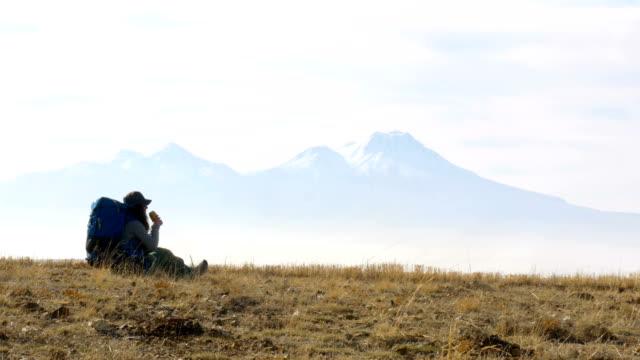 バックパッカーはカッパドキアの谷の標高の高い山を見ながらコーヒーを飲んでください。 - お茶の時間点の映像素材/bロール