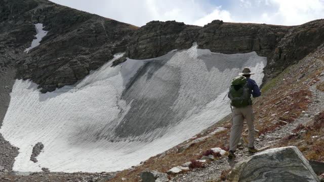 Backpacker man hiking Indian Peaks Wilderness Sawtooth Mountain snowfield Colorado video