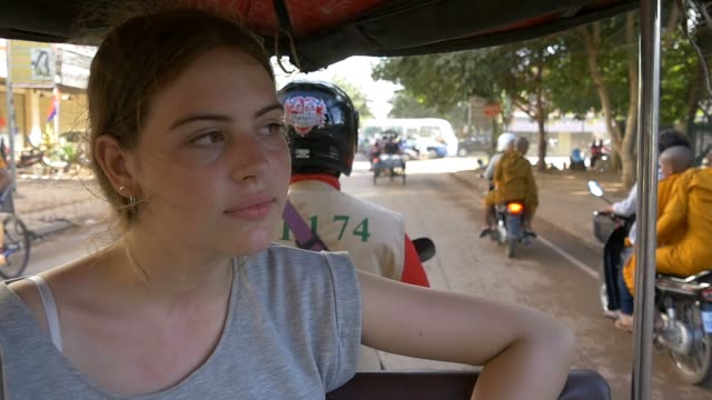 Backpacker tourist girl traveling in asia riding on tuk tuk rural asain villag video