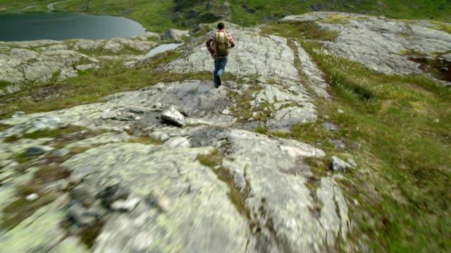 backpacker trekking. man running on rocky coast. drone point of view - турист с рюкзаком стоковые видео и кадры b-roll