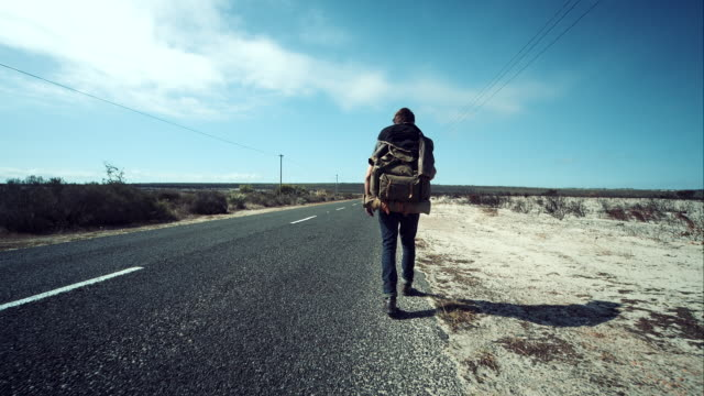 Backpacker walking along road video