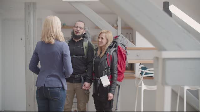 4K: Backpackers Renting Apartment. Young Hipster Couple, backpackers rented apartment using vacation home rental services online. Talking to host and getting keys. Host welcome them to her renting apartment. Shot with Sony FS700R with Odyssey7Q native ProRes422HQ television host stock videos & royalty-free footage