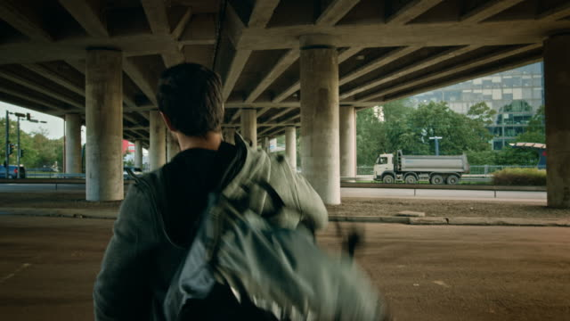backshot of an athletic young man walking towards the road under a bridge in an urban environment. he's wearing a grey hoodie and a sports bag. - podążać za czynność ruchowa filmów i materiałów b-roll