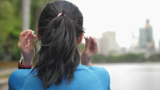 backside footage of a girl putting on the headphones - vestirsi video stock e b–roll