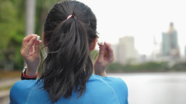 backside footage of a girl putting on the headphones - cuffia attrezzatura per l'informazione video stock e b–roll