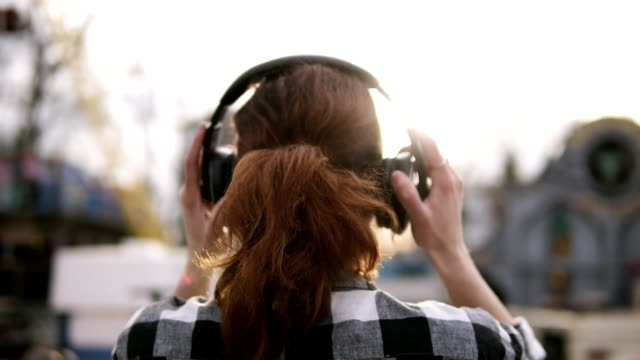 backside footage of a girl with a brown haired tail standing a plaid shirt oover against the shining sun. putting on the headphones - słuchawka nauszna filmów i materiałów b-roll