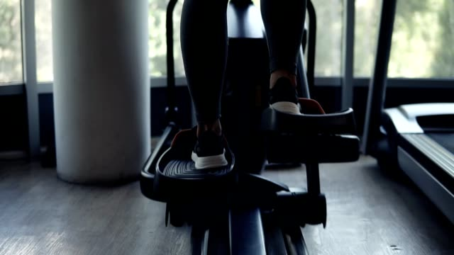vídeos de stock e filmes b-roll de backside footage of a gorgeous athletic young woman workout at gym on x trainer in black sneakers, leggings and black sport bra. fitness, loosing weight concept - aparelho de musculação