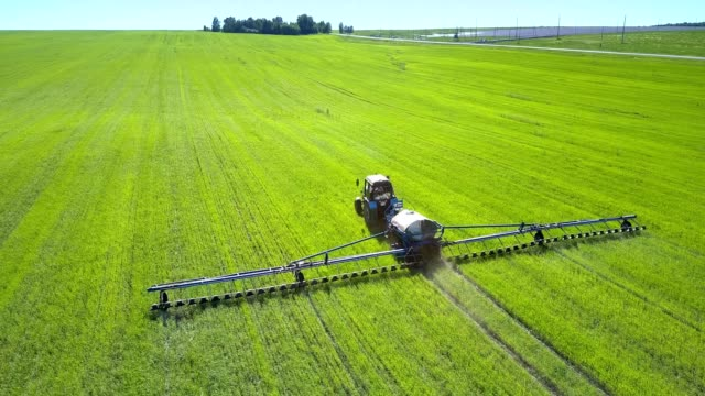 backside tractor field sprayer drives on field to wood - agricultural machinery stock videos & royalty-free footage