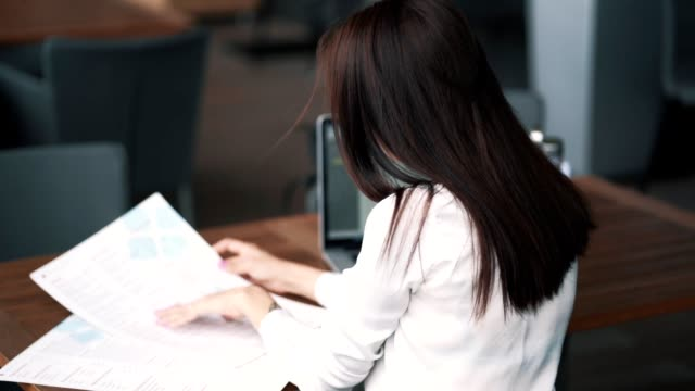 Backside view, girl freelancer looks at menu in cafe, laptop on table, slow motion