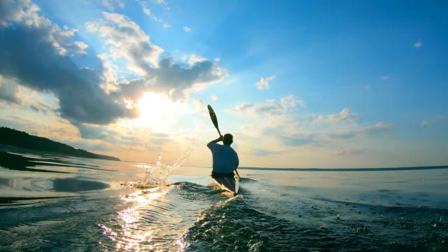 vidéos et rushes de vue arrière d'un homme naviguant sur un canot - kayak