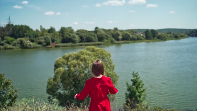 backside view of pretty woman near the river. - длина стоковые видео и кадры b-roll