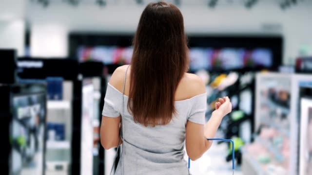 Backside view, woman goes on a cosmetics store with basket, slow motion