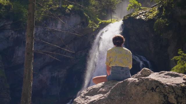 Rückseite Blick junge Frau sitzt auf großen Felsen Wasserfall-streaming von Klippe zu betrachten – Video