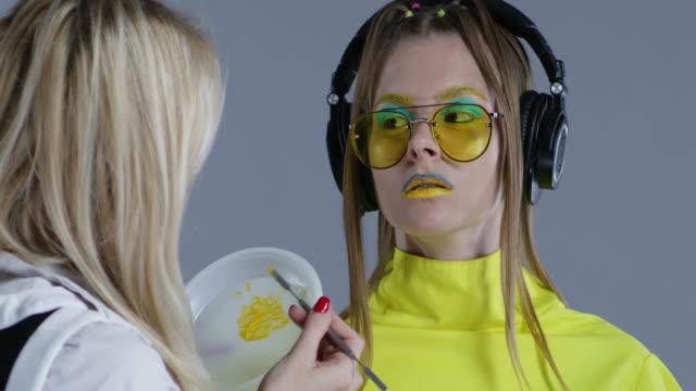 backstage. make-up artist sätter gul läppstift på modellens läppar. modellen bär gula solglasögon och stora trådlösa hörlurar. fashion video. - makeup artist bildbanksvideor och videomaterial från bakom kulisserna