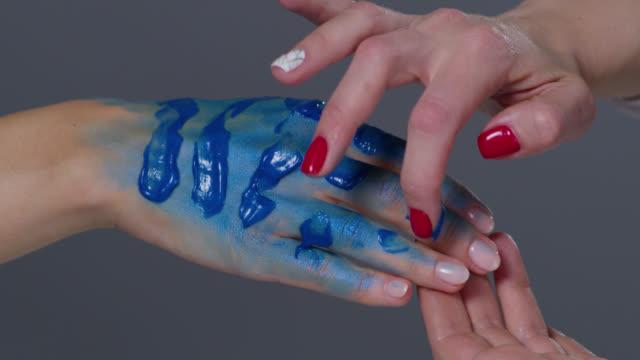 backstage of a make-up artist, putting blue glowing paint on model`s hand. fashion video. - гримировальные краски стоковые видео и кадры b-roll