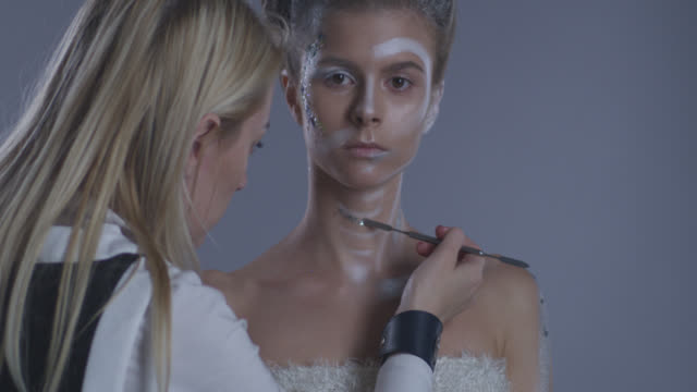 backstage of a make-up artist putting glitter on blond high fashion model in stage make-up. fashion video. - clavicola video stock e b–roll