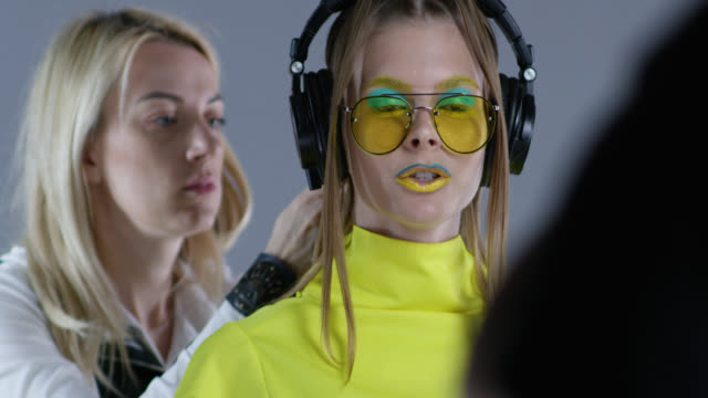 Backstage of hairdresser fixing high fashion model`s hair. Model wears yellow sunglasses and black leather gloves, big wireless headphones. Model talks to director. Fashion Video. Backstage of hairdresser fixing high fashion model`s hair. Model wears yellow sunglasses and black leather gloves, big wireless headphones. Model talks to director. Fashion Video. Slow Motion. 4K 30fps ProRes 4444 supermodel stock videos & royalty-free footage