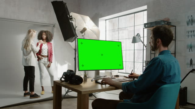 Backstage of the Photoshoot: Make-up Artist Applies Makeup on Beautiful Black Girl. Photo Editor Works on Desktop Computer with Green Mock-up Screen Display. Fashion Internet Magazine