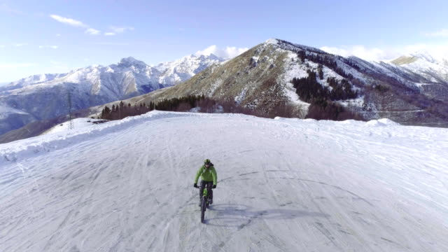 backward aerial over biker man cycling on snowy path during winter with mtb e-bike. Cyclist on bike on snow outdoors in winter. 4k drone flight video video