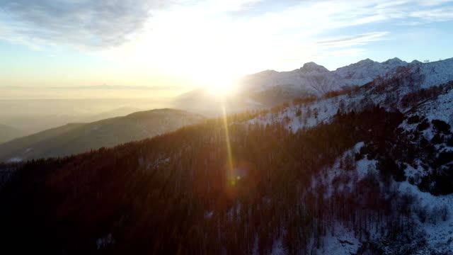 Backward aerial top view over winter snowy mountain and woods forest at sunset or sunrise.Dusk or dawn twilight sunshine flare.Mountains snow season sun establisher.4k drone flight establishing shot video