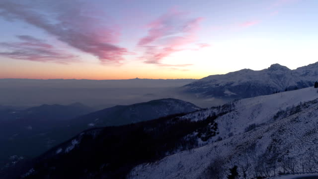 Backward aerial top view over winter snowy mountain and woods forest at sunset or sunrise.Blue hour dusk or dawn twilight Alps mountains snow season establisher.4k drone flight establishing shot video