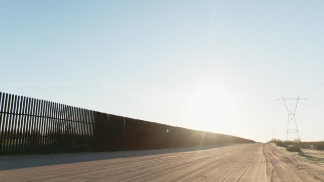 明るく澄んだ晴れた日にメキシコと米国の間のスチールスラット国境の壁(米国側)の隣の未舗装道路に沿って後ろ向きに移動ドローンショット - 壁点の映像素材/bロール