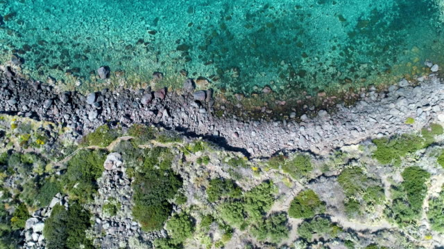 backward overhead aerial on mediterranean sea wild coast, blue water.Nature environment outdoors travel establisher,Italy,Sicily Salina Eolian Island.Sunny summer.4k drone top view establishing video video