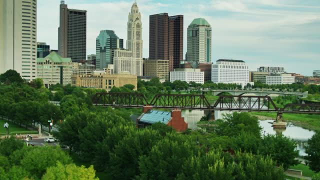 backwards descending drone shot of downtown columbus over lush green trees - columbus day filmów i materiałów b-roll