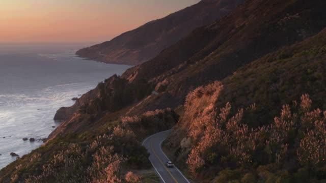 vídeos de stock e filmes b-roll de backwards drone flight over big sur, california - montanha costeira