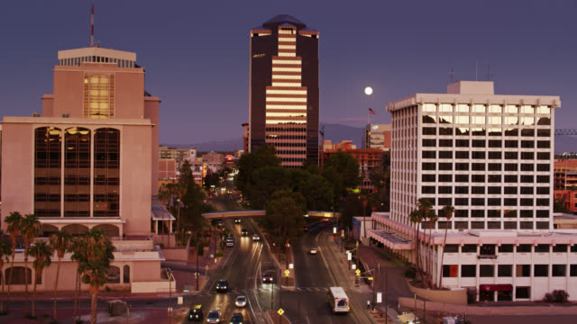 Backwards Drone Flight Over Downtown Tucson Street at Twilight with Full Moon