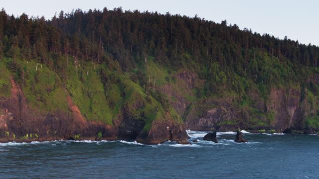 vídeos de stock e filmes b-roll de backwards drone shot of cape lookout, oregon - montanha costeira
