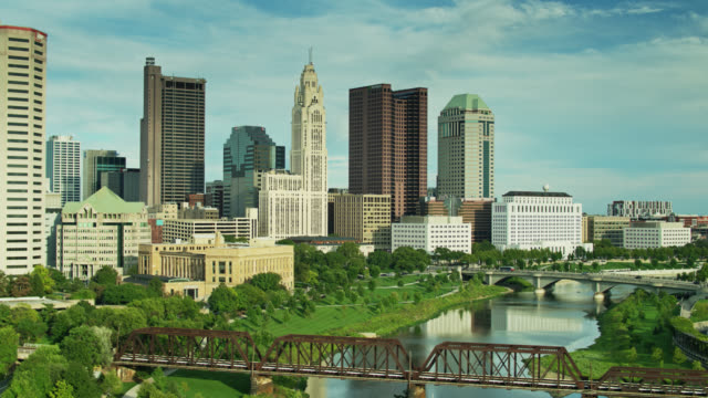backwards drone shot of downtown columbus from over the scioto river - columbus day filmów i materiałów b-roll