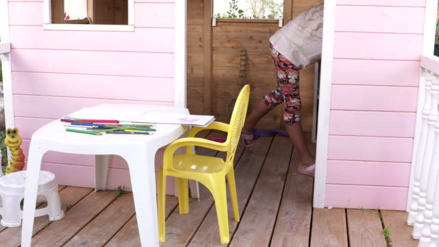 Backyard playground kids play house. Children playing in wooden pink playhouse. video