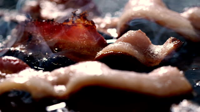 vídeos de stock e filmes b-roll de bacon frying slow motion panning macro - macro