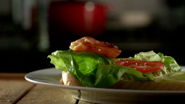 Bacon rashers slowly falling onto a sandwich. video