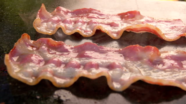 Bacon strips are fried and grilled video