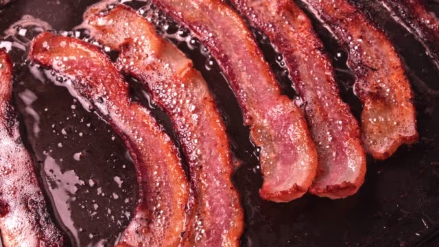 Bacon Bacon cooking on a flat pan to perfection. bacon stock videos & royalty-free footage