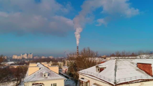 schlechte ökologie. das kraftwerk befindet sich in der mitte von einem wohnquartier, wirft rauch aus dem hohen rohr, verschmutzung der atmosphäre der stadt. luftbild-drohne video mit absteigender bewegung der kamera. - weißrussland stock-videos und b-roll-filmmaterial