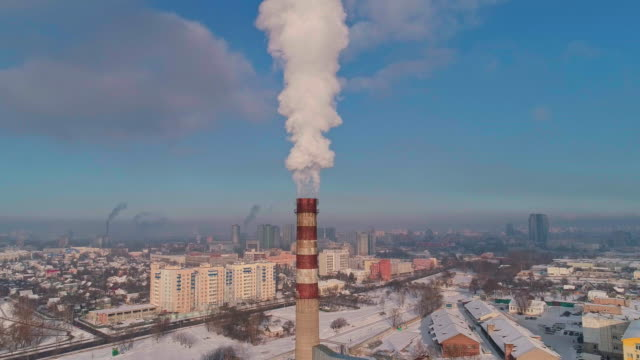 bad ecology. the thermal power plant located in the center of the residential district, throws out smoke from the high pipe, polluting the atmosphere of the city. aerial drone video with ascending camera motion. - centrale termoelettrica video stock e b–roll