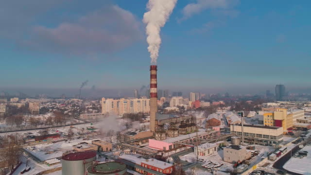 bad ecology. the thermal power plant located in the center of the residential district, throws out smoke from the high pipe, polluting the atmosphere of the city. aerial drone video with backward camera motion. - centrale termoelettrica video stock e b–roll