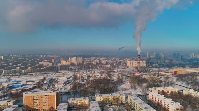 bad ecology. the thermal power plant located in the center of the residential district, throws out smoke from the high pipe, polluting the atmosphere of the city. aerial drone video with static camera.. - centrale termoelettrica video stock e b–roll